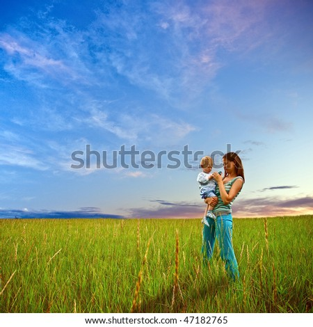 mother and son standing on field - stock photo