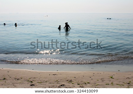 Mother and son swimming in the sea in the morning, beautiful sunlight