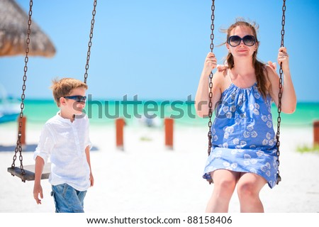 Mother and son swinging with tropical beach on background - stock photo