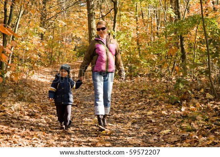 Mother and son taking a walk in autumn forest - stock photo