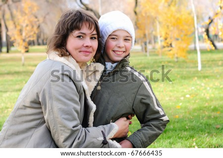 Mother and son together having fun in autumn park - stock photo