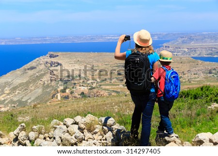 mother and son travel hiking in mountains, family tourism