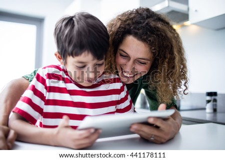 Mother and son using digital tablet in kitchen at home - stock photo