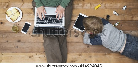Mother and son using tablet and laptop - stock photo
