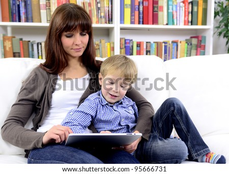 mother and son using tablet with touchscreen together reading an ebook - stock photo