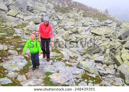Mother and son walking a thin trail above rocky mountain slope - stock photo