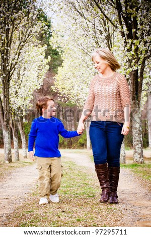 Mother and son walking hand in hand  at park during spring with blooming trees - stock photo