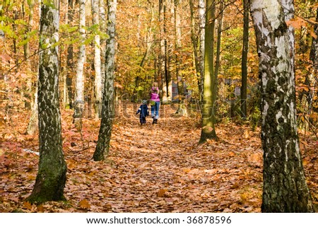 Mother and son walking in colorful autumn forest - stock photo