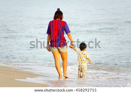 mother and son walking on morning beach,select focus with shallow depth of field