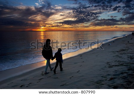 Mother and son walking on the beach and watching colorful sunset - stock photo