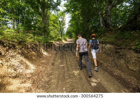 Mother and son walking through the forest on a muddy road