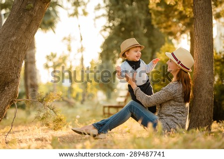 Mother and son wearing a hat sitting in the park under a tree, family happiness - stock photo