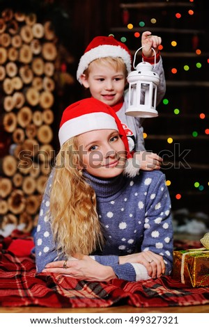 mother and son wearing red Santa Claus caps lying on a checkered blanket on the background of Christmas lights. Baby boy in a Christmas hat holding a flashlight
