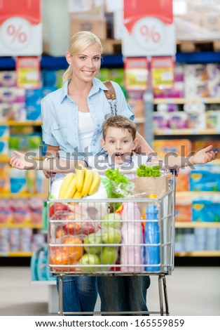 Mother and son whose arms are outstretched keeps cart full of products in shop. Concept of healthy food and consumerism - stock photo