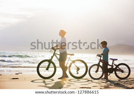Mother and son with bikes on a beach at sunset - stock photo
