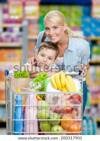 Mother and son with cart full of products in market. Concept of healthy food and consumerism - stock photo