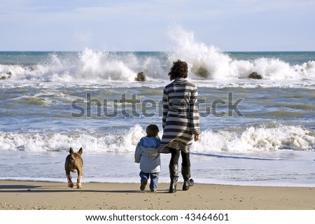 Mother and son with dog on the beach. - stock photo