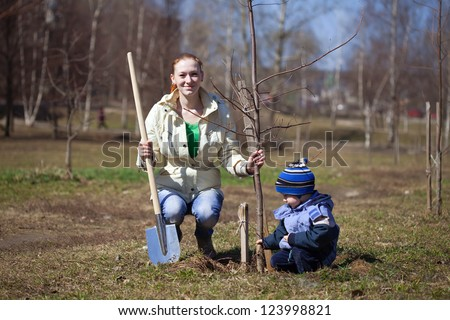 mother and son with spade outdoors planting  tree - stock photo