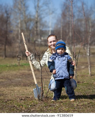 mother and son with spade outdoors planting  tree