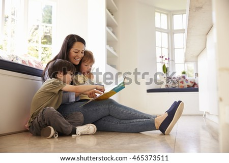 Mother And Sons Reading Story At Home Together