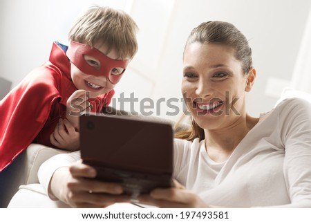 Mother and superhero child playing videogames together in the living room. - stock photo