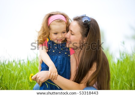 Mother and sweet curly girl on the meadow - stock photo