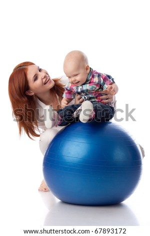 Mother and sweet small baby with fitness ball on a white background. - stock photo