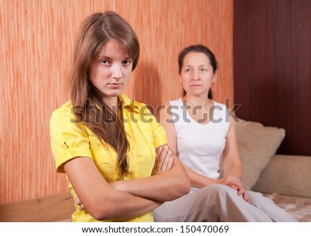 Mother and teen daughter having quarrel at home - stock photo