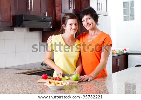 mother and teen daughter making fruit salad in kitchen - stock photo