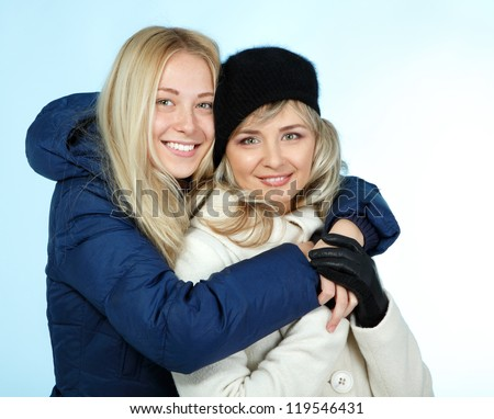 Mother and teen daughter winter portrait over blue