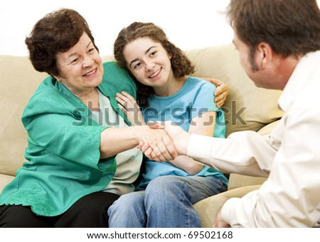 Mother and teen girl shake hands with a counselor. - stock photo