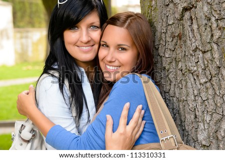 Mother and teen hugging outdoors relaxing smiling daughter bonding loving - stock photo