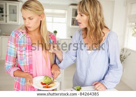 Mother and teenage daughter arguing about housework - stock photo