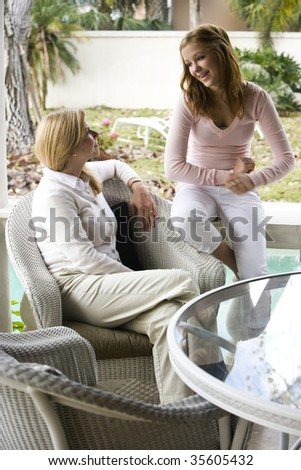 Mother and teenage daughter chatting together on patio - stock photo