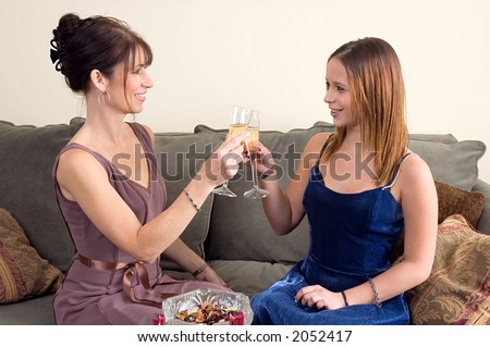 Mother and Teenage Daughter, dressed in formal wear (perhaps a dinner party, perhaps daughter is going to a prom), toasting each other.