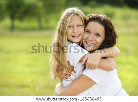 Mother and teenage daughter hugging and smiling together in summer garden. - stock photo