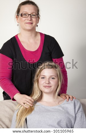 Mother and teenage daughter looking at each other friendly. Mother is standing behind the girl who is sitting down - stock photo