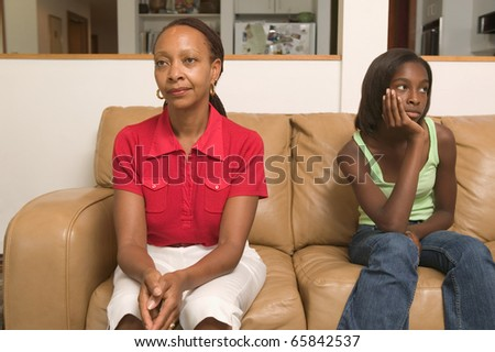 Mother and teenage daughter sitting on couch