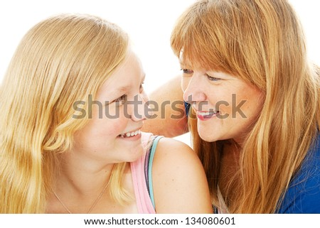 Mother and teenage daughter smile at each other lovingly.  White background. - stock photo