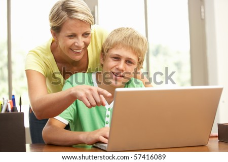 Mother And Teenage Son Using Laptop At Home - stock photo
