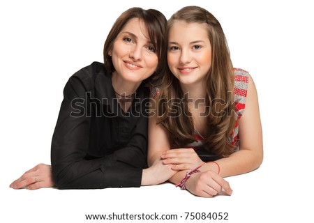 Mother and teenager daughter lying down over white background - stock photo