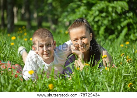 Mother and teenager son laying on the green grass