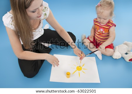 Mother and the daughter draw paints the sun.  Isolated  blue. - stock photo