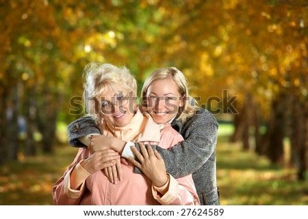 Mother and the daughter embrace in autumn park - stock photo