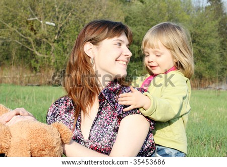 Mother and the daughter play on a meadow grass in park - stock photo