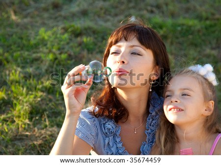Mother and the  little daughter in a park - stock photo
