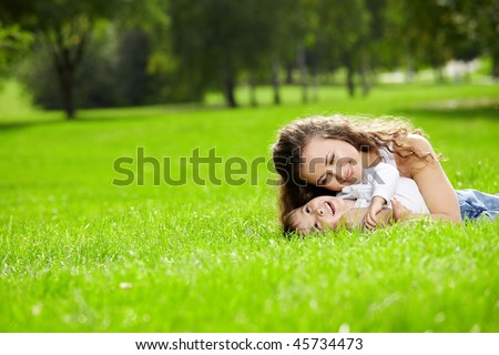 Mother and the small son lie on a summer lawn - stock photo