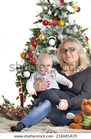 Mother and their small child sits near Christmas tree with teddy bear - stock photo