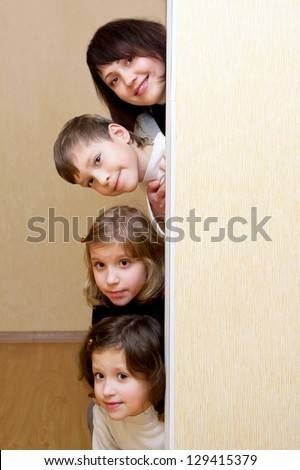 Mother and three children peeking of the door. - stock photo