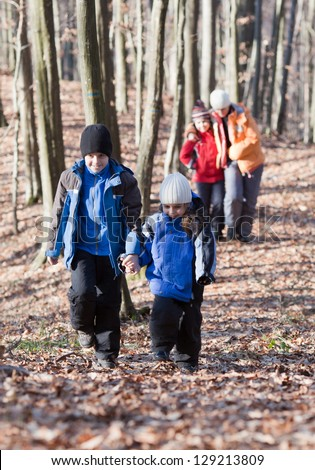 Mother and three children walking in the woods - stock photo